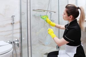 a woman cleaning shower doors from soap