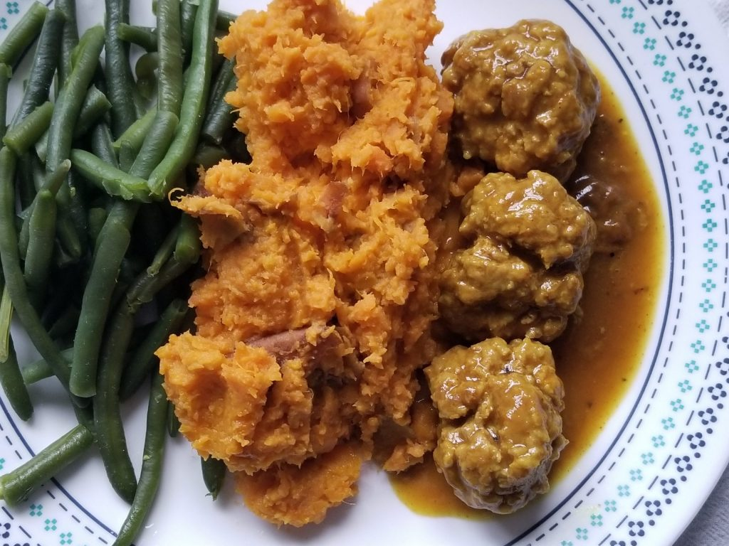 A plate filled from left to right with green beans, mashed sweet potatoes, and curry meatballs with gravy.