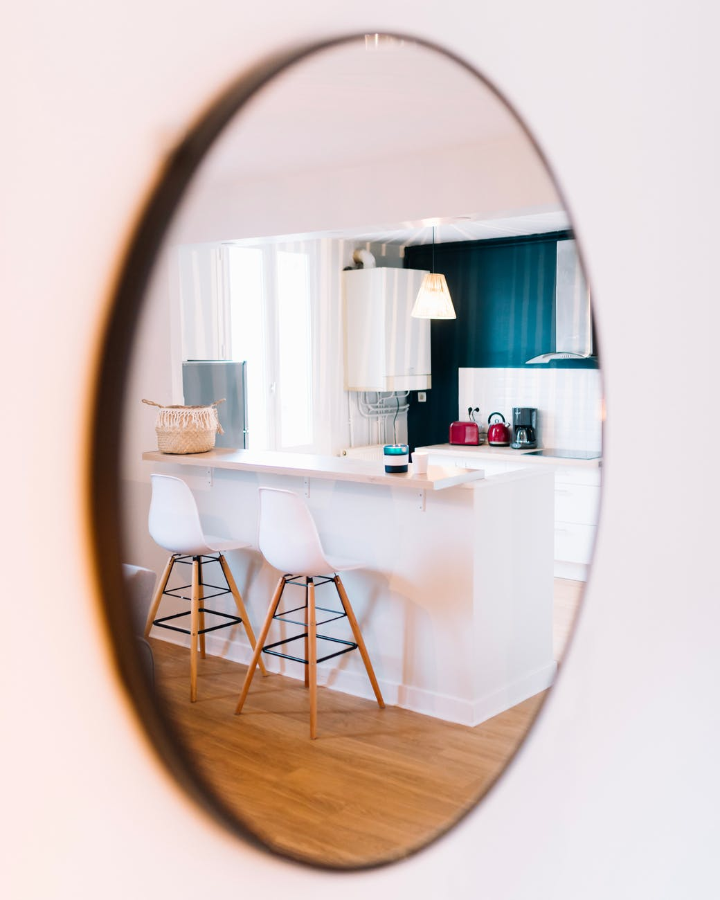 white wooden table and chairs seen from oval mirror