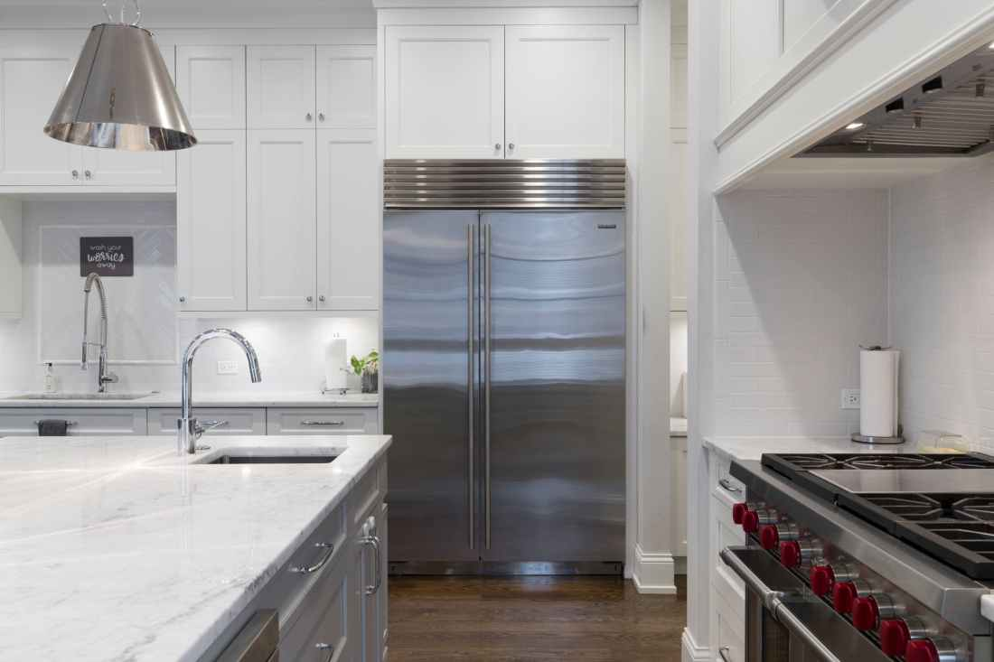 stainless steel refrigerator beside white kitchen cabinet