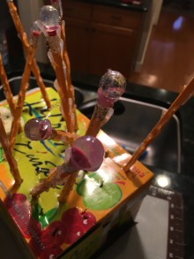 Pencils with marbles on top and hot glue designs drying.