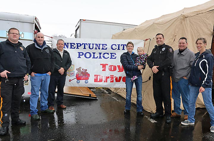 Neptune City police collected for the Toys for Tots program recently at the Neptune City Shopping Center. Pictured were Police Officers Mark Mazzeo (left) and Janell Pyzik (right) with Navy and Andrew and Aly Reynolds, all of Neptune.