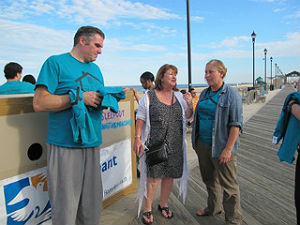 Coaster Photo - Marilyn Schlossbach (right) and Joe Leone talk to a supporter on the Asbury Park boardwalk this week. They are sleeping out in cardboard boxes to raise money for homeless youths.