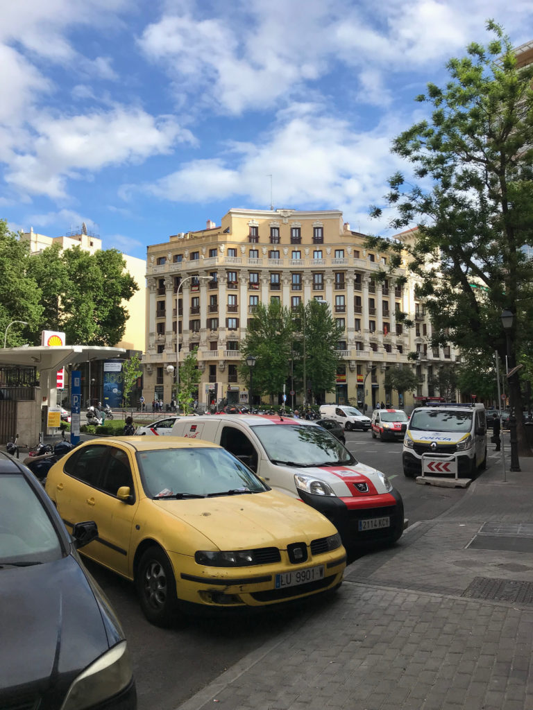yellow car in front of beige building