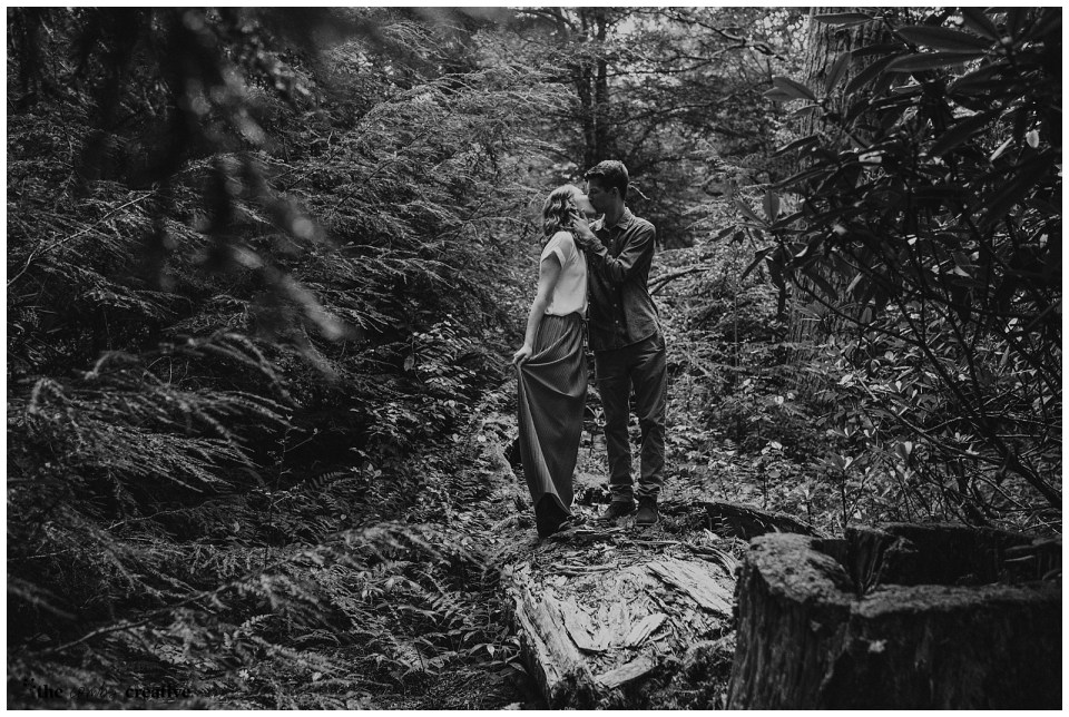 Couple standing in a forrest, kissing on a log.