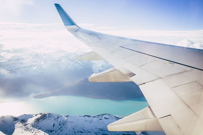 White airplane wing over river and snowy mountains