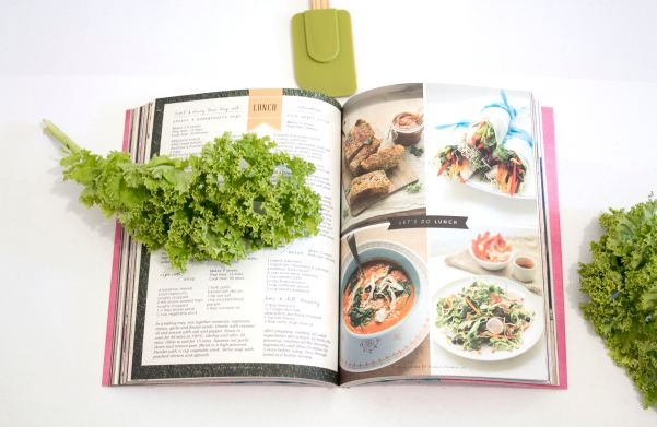 cookbook, kale, and spatula on table