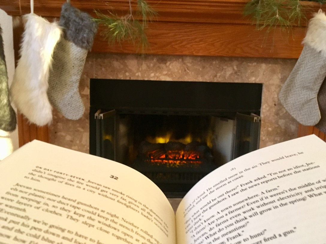 Open book sitting in front of fireplace with Christmas stockings