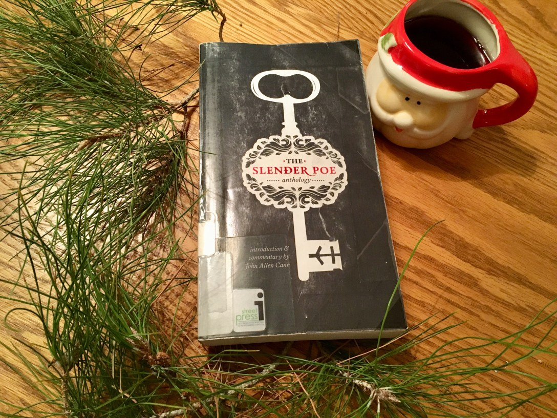 The Slender Poe Anthology paperback on wood table next to pine needles and coffee in Santa mug