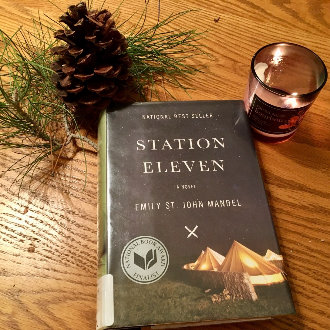 Station Eleven hardback sitting on wood table next to pine needles, a pine cone, and a candle