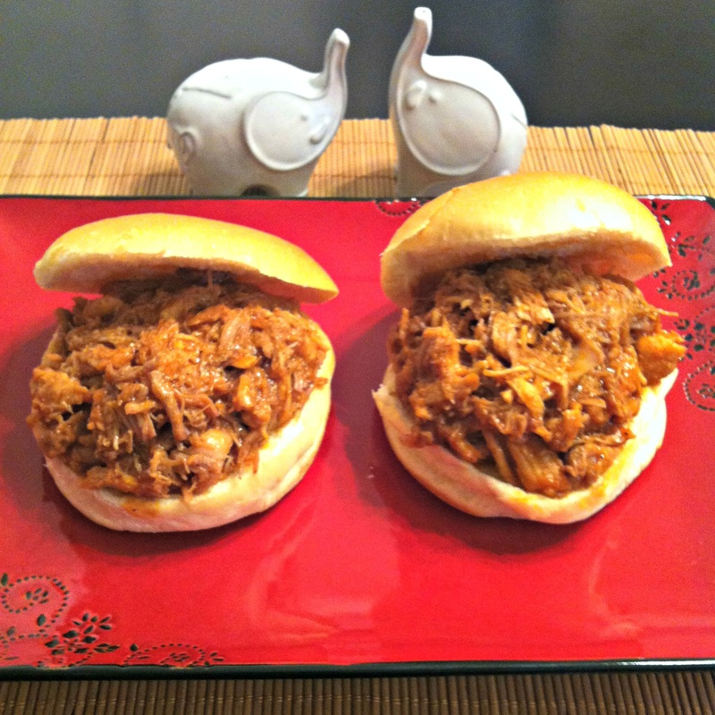 Red plate of two buns filled with pulled pork.