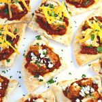 BBQ Chicken Pita Bites ~ Toasted Pita bread slathered with tomato bacon jam and chopped BBQ chicken pieces, then finished with cilantro and bleu or cheddar cheese.