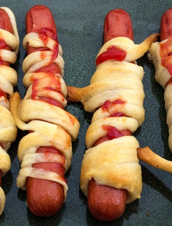 Hot dogs carved to look like fingers wrapped in bandages made from crescent rolls drizzled in ketchup for blood.