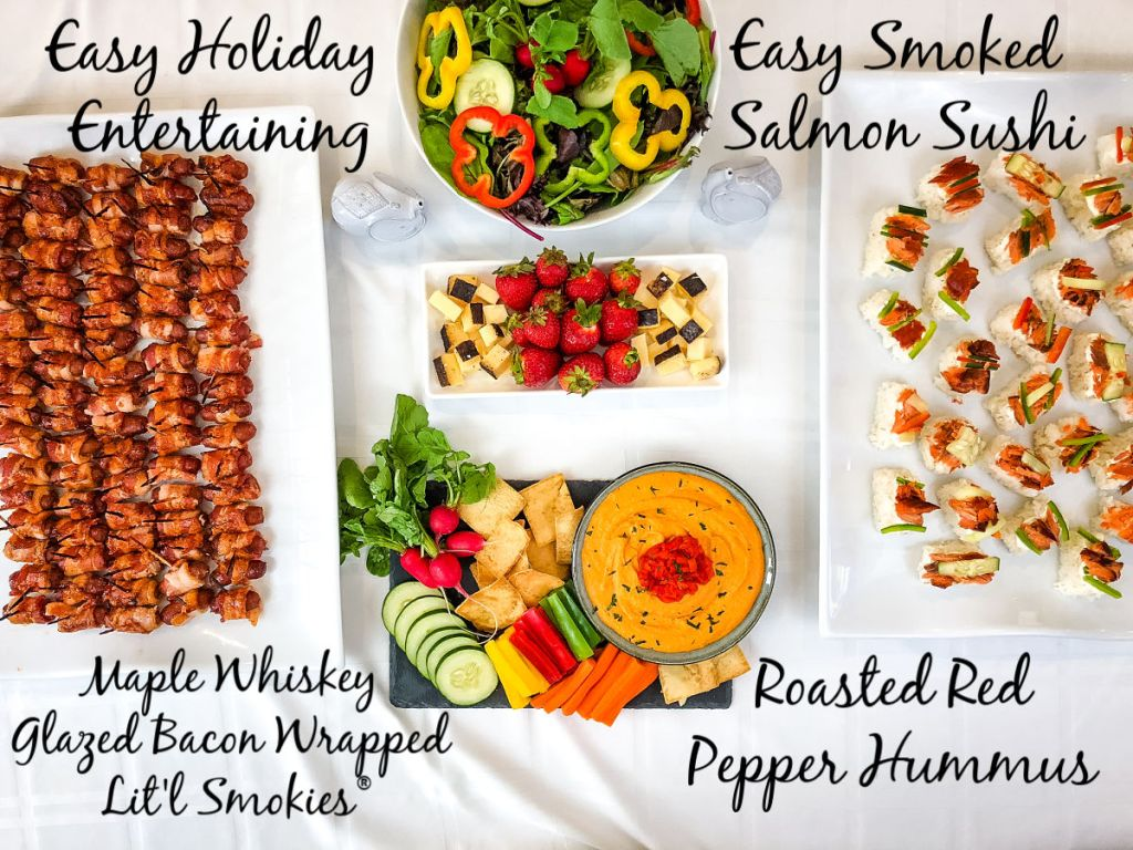 Overhead image of a table filled with appetizers. Roasted red pepper hummus, easy smoked salmon sushi, mini sausages, salad, and fruit and cheese plate.