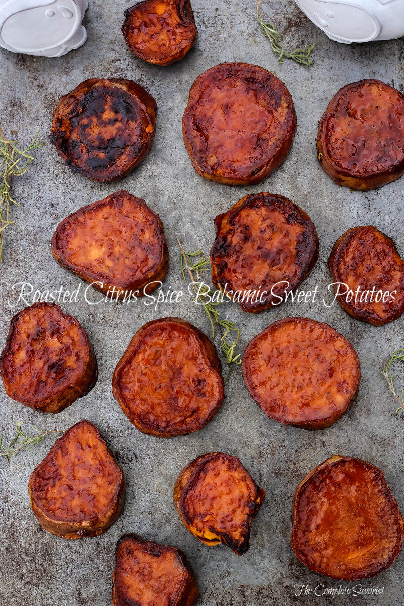 Thick coin-sliced sweet potatoes have been roasted in a glaze from citrus spice balsamic vinegar on a silver tray with fresh rosemary garnish.