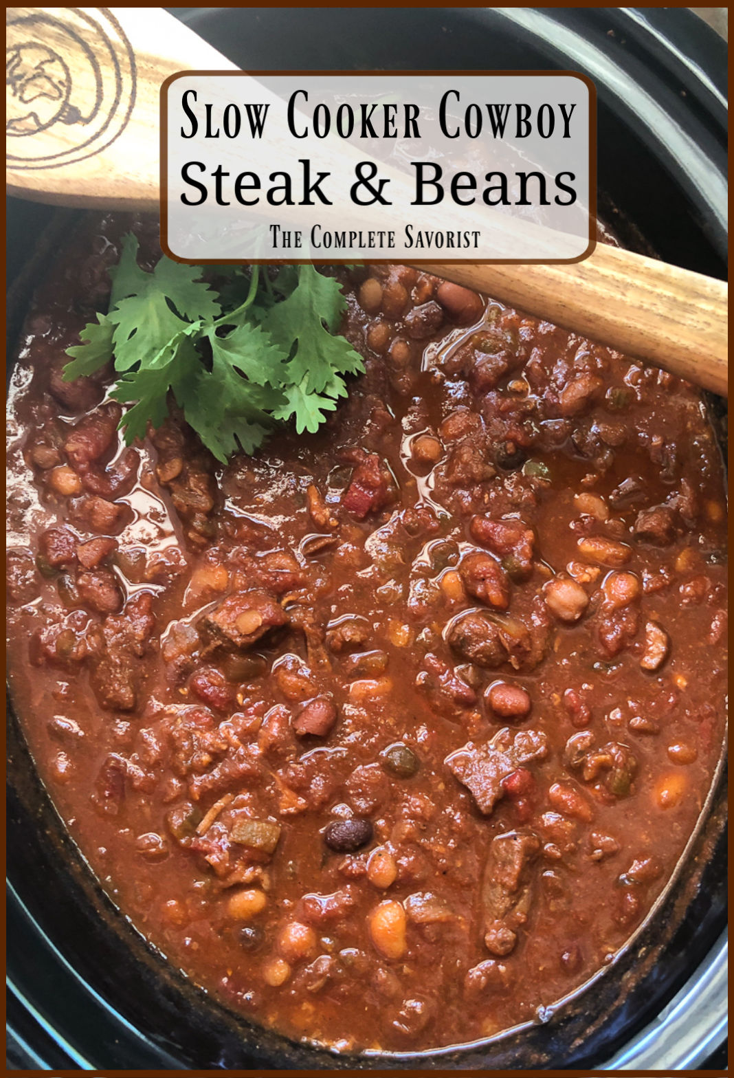 Slow Cooker Cowboy Steak and Beans in the crock garnished with fresh cilantro and a wooden spoon with website logo.