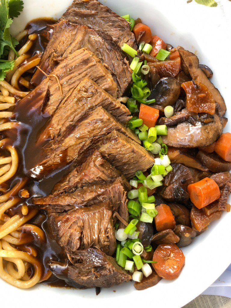 Close up view of the Japanese pot roast surrounded by udon noodles, vegetables, gravy, and garnishes of cilantro and green onions.