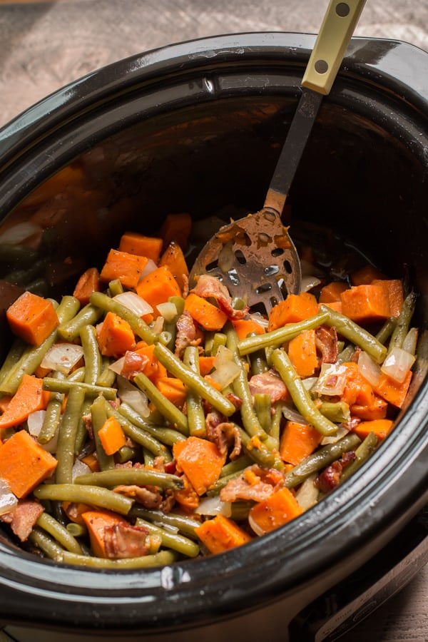 Slow cooker crock of sweet potatoes, green beans, bacon, and onions with a serving spoon.