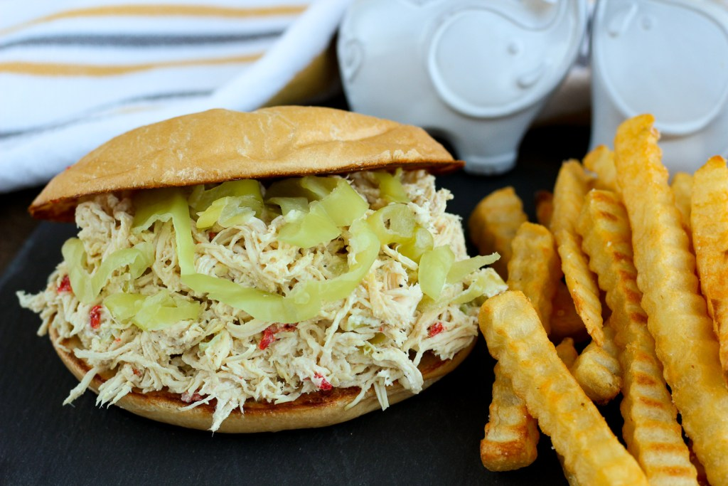 An over stuffed sandwich filled with shredded chicken with pepperoncini peppers and pimentos served with french fries; white elephants and a cloth napkin visible in the background.