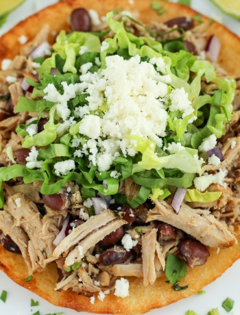 Top view of the pork and black bean tostada garnished with lettuce and queso fresco.