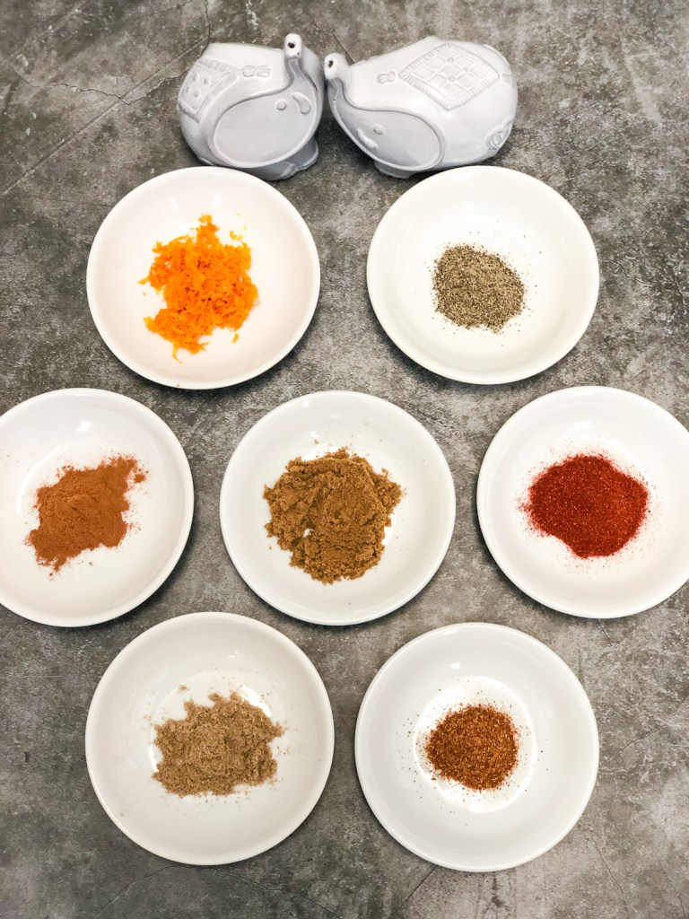 7 white bowls individually filled for this Moroccan spice blend: cumin, coriander, cayenne, paprika, cinnamon, pepper, and orange zest. Not pictured is salt.