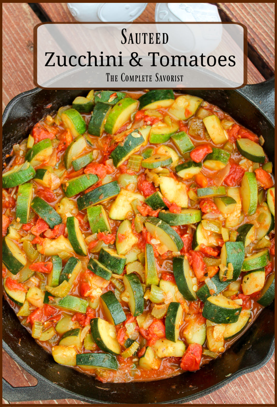 Cast iron skillet with Italian style zucchini, tomatoes, onions, and celery.