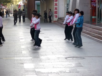 Staff from shops doing their morning execise on the footpath outside their premises in Dunhuang
