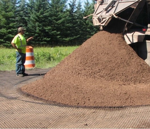 Placing Aggregates over the Geogrid layer for Pavement Construction