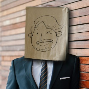 image of J R H Lawless wearing a paper back over his head, drawn on to look like a smiling, winking face