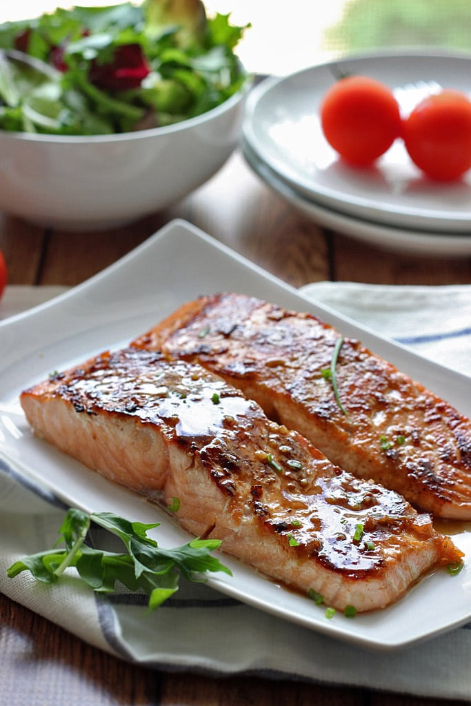 Two fillets of honey garlic salmon on a white plate.