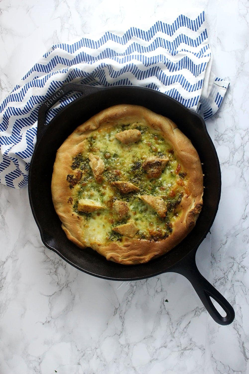 This rocket pesto chicken skillet pizza is a brilliant variation on a classic pizza. With a pesto base and a layer of mozzarella surrounding bits of chicken