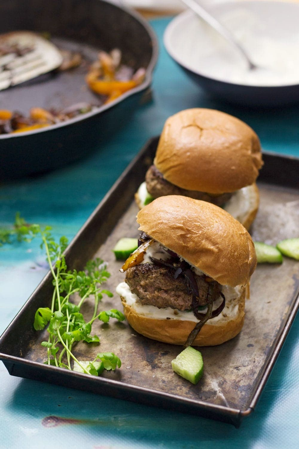 These Greek lamb burgers are served in a brioche bun. Topped with caramelised pepper and onion, refreshing cucumber and a drizzle of garlicky Greek yoghurt!