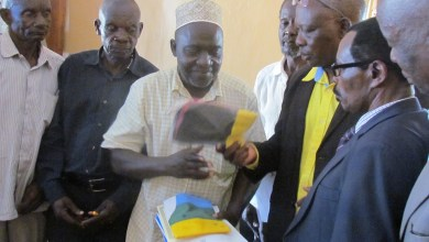 Members of the elders Sacco admiring their certificate which was recently given to them.