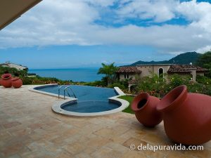 View of an infinity pool and the Pacific Ocean from the patio of a hillside house in Costa Rica.