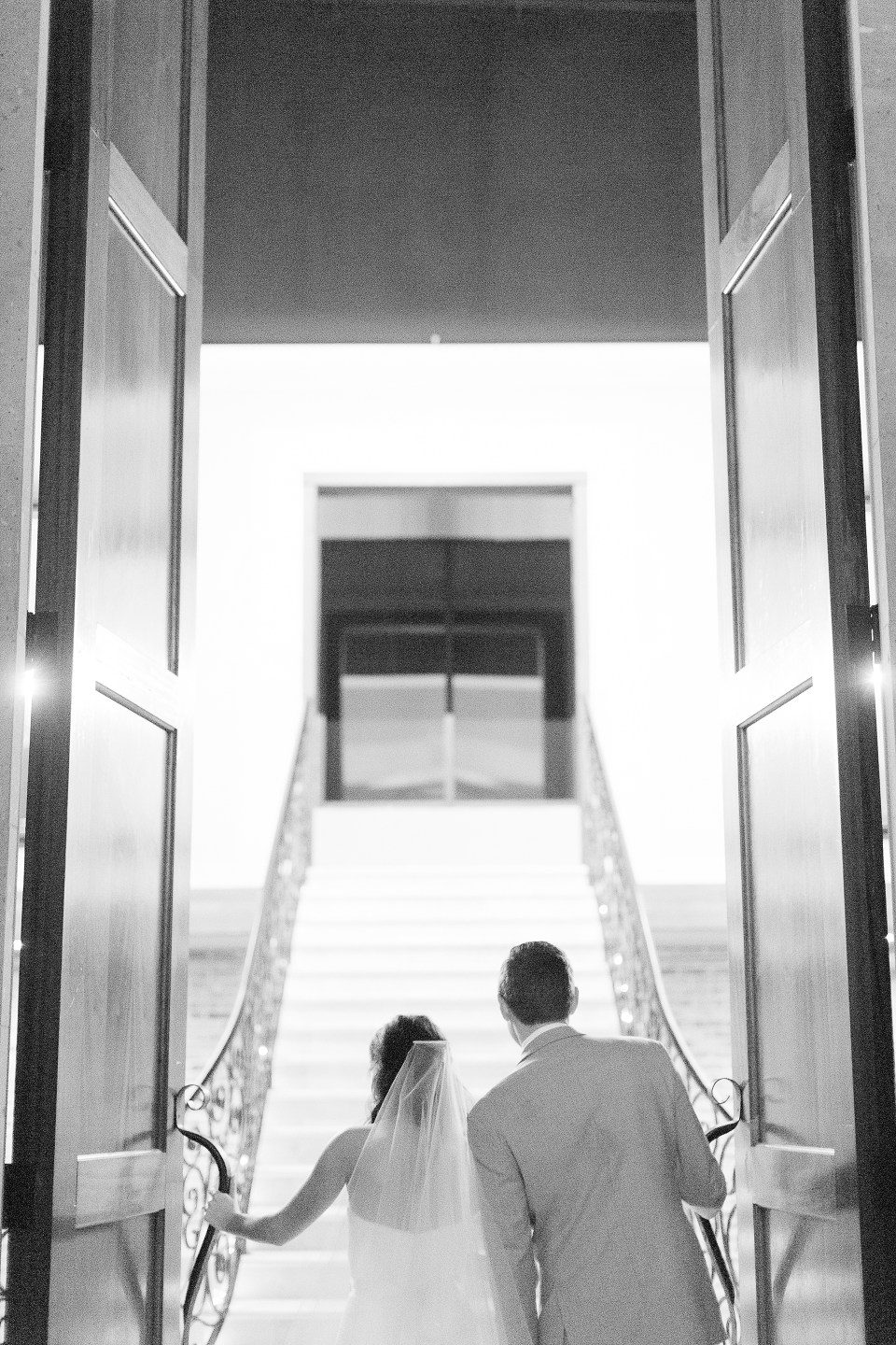 black and white photo of bride leading groom up stairs