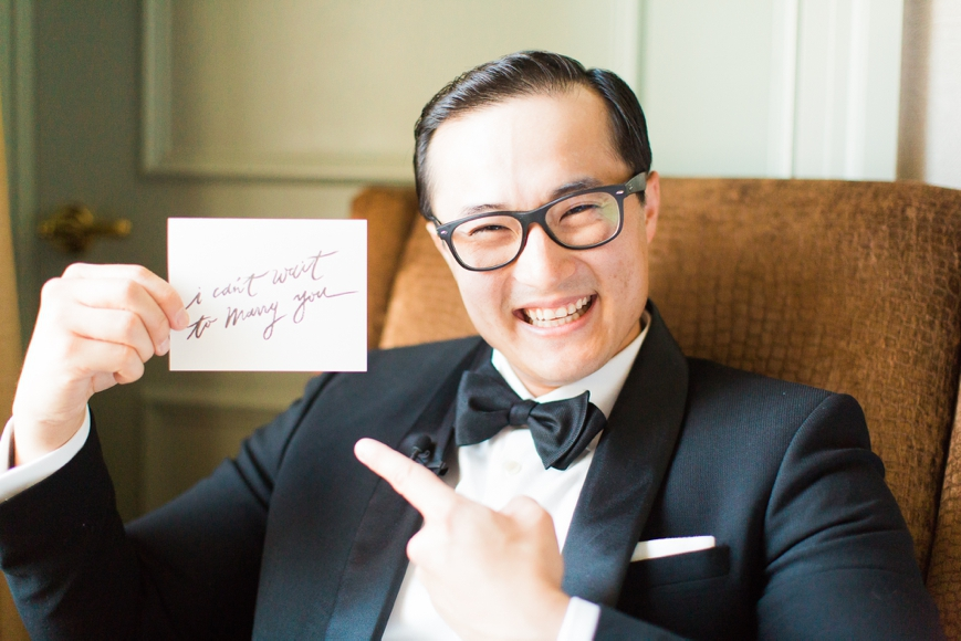 groom smiling holding letter to wife