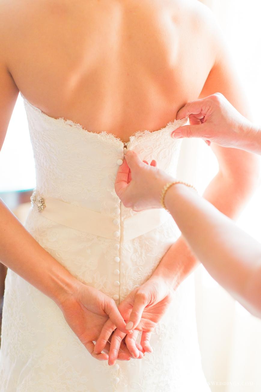 mother zipping up bride's dress