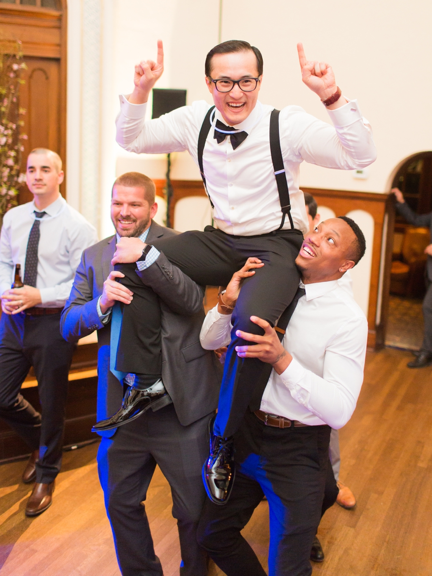 friends lift groom up on their shoulders