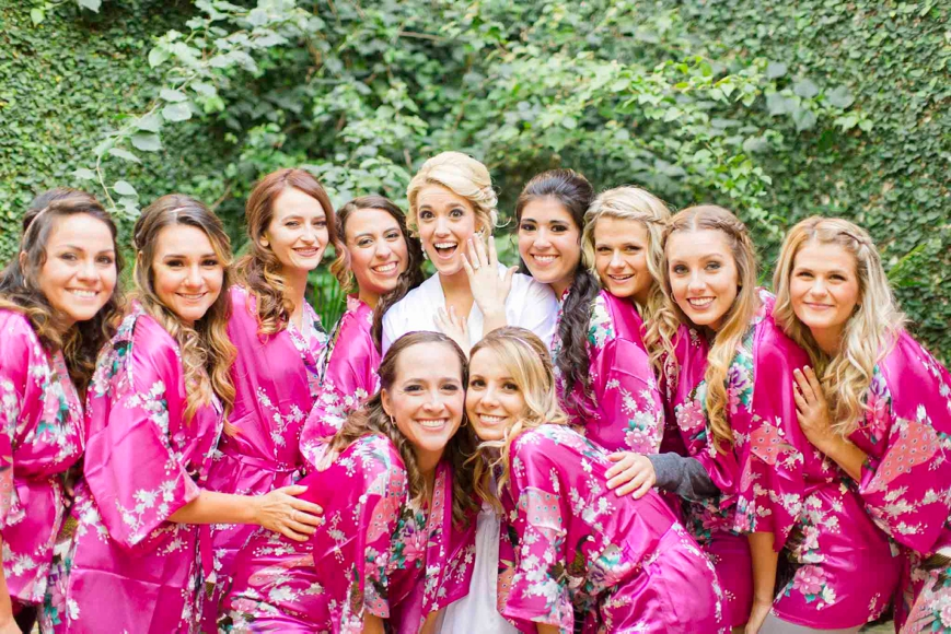 bride with bridesmaids in pink robes