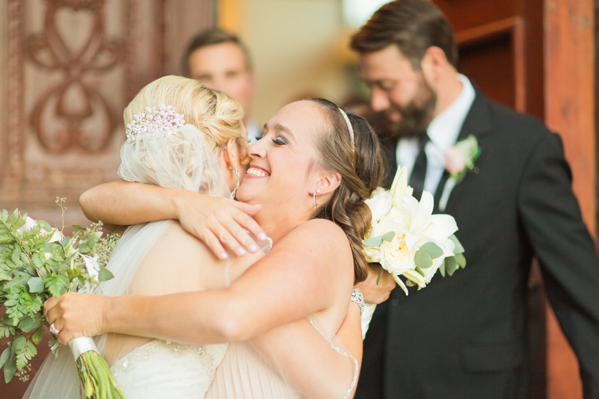 happy bridesmaid hugging bride