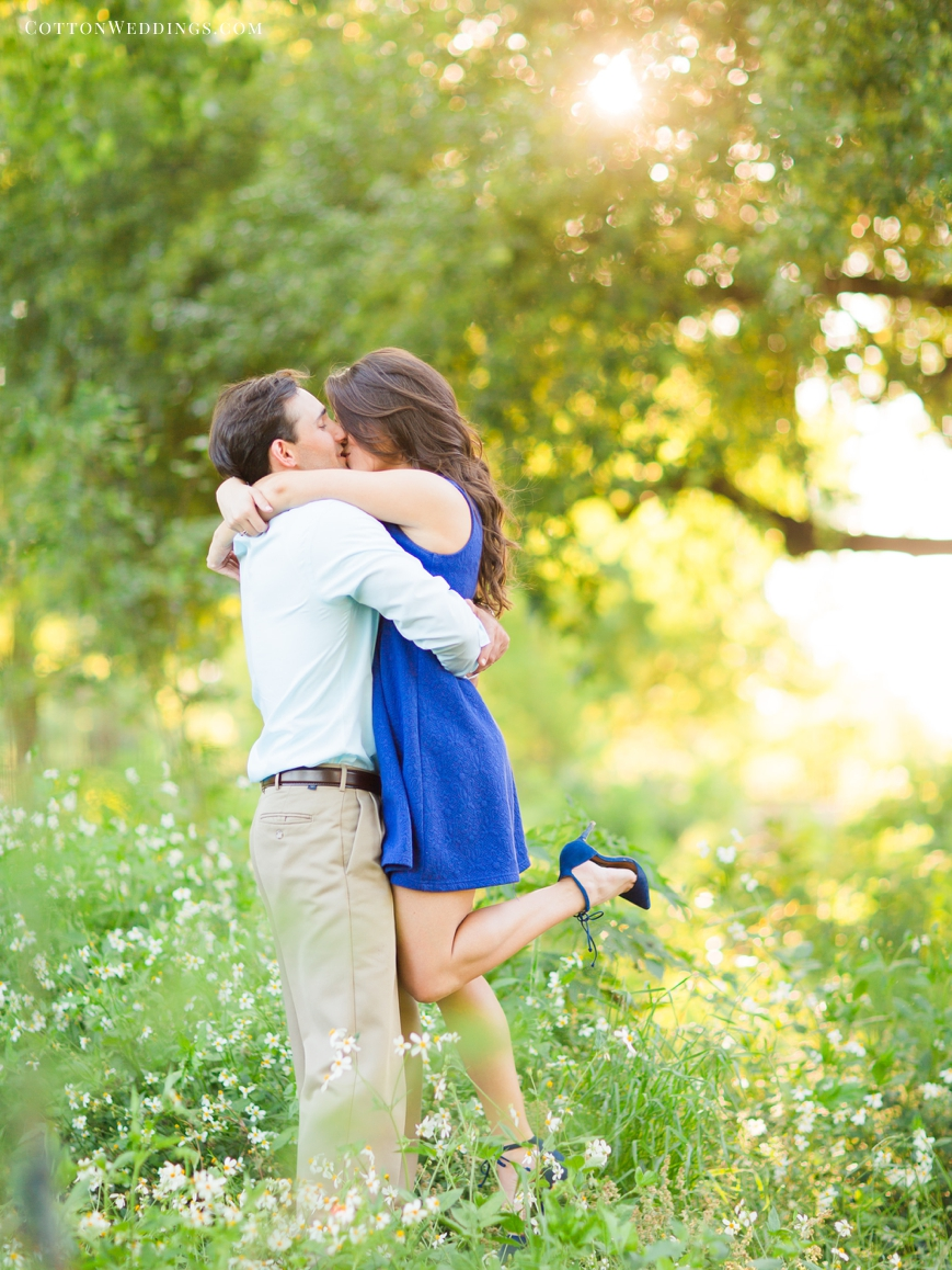 engaged couple hugging sweetly in wildflowers