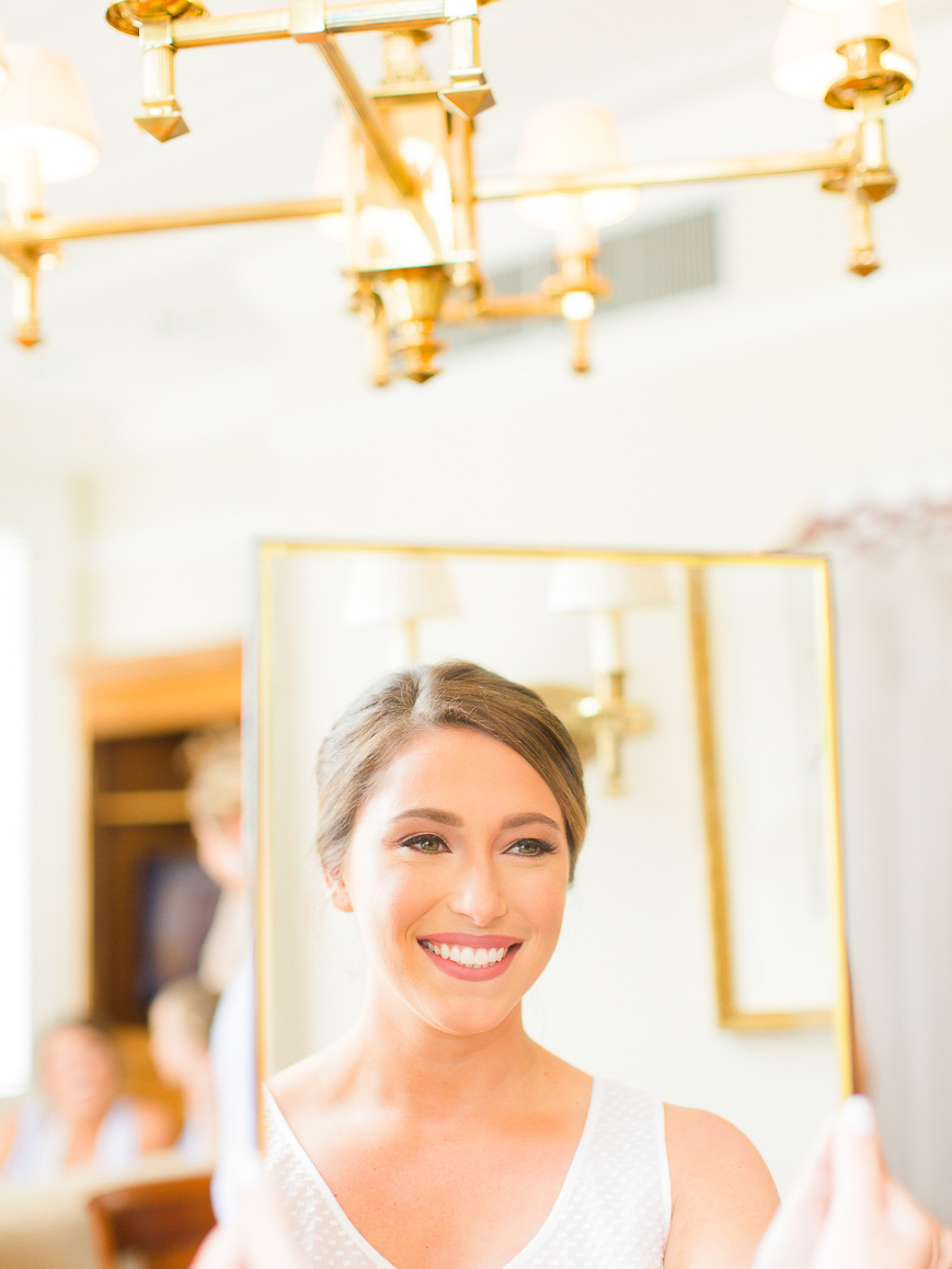 happy bride smiling at herself in mirror