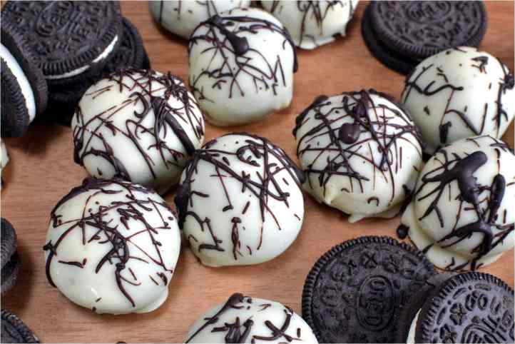 Oreo Balls covered in white chocolate with milk chocolate drizzled on top.
