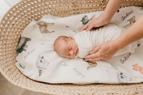 Person tucking in a sleeping newborn baby