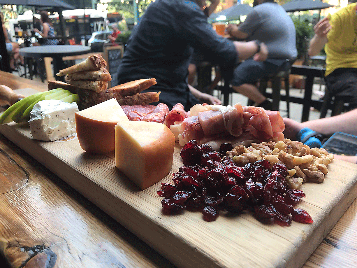 meat and cheese board with people seated in the background