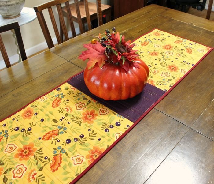 Pumpkin Spice Table Runner made by Julie Cefalu @ The Crafty Quilter. It's a simple design that packs a punch and it's perfect for the Fall holidays.
