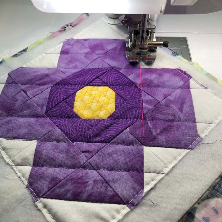 Blossom Mug Rug made and designed by Julie Cefalu @ The Crafty Quilter using her free Blossom Quilt Block tutorial.  Showing the Laser guide beam on a Babylock Crescendo for quilting.