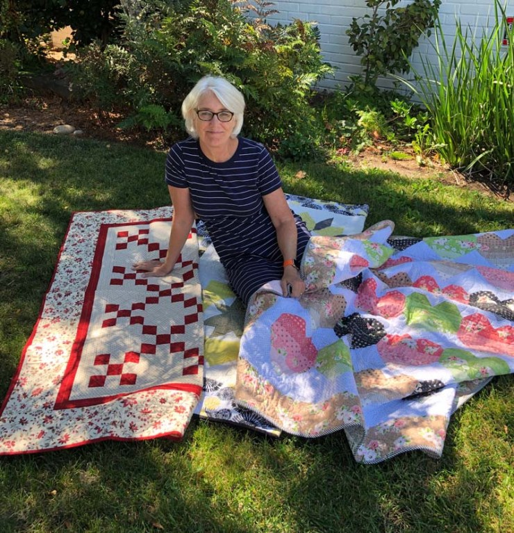 Julie Cefalu surrounded by her quilt donations for Bike Angels United.