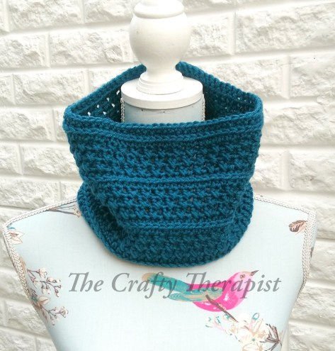 Teal Cowl Crochet Pattern on tailors dummy white brick background