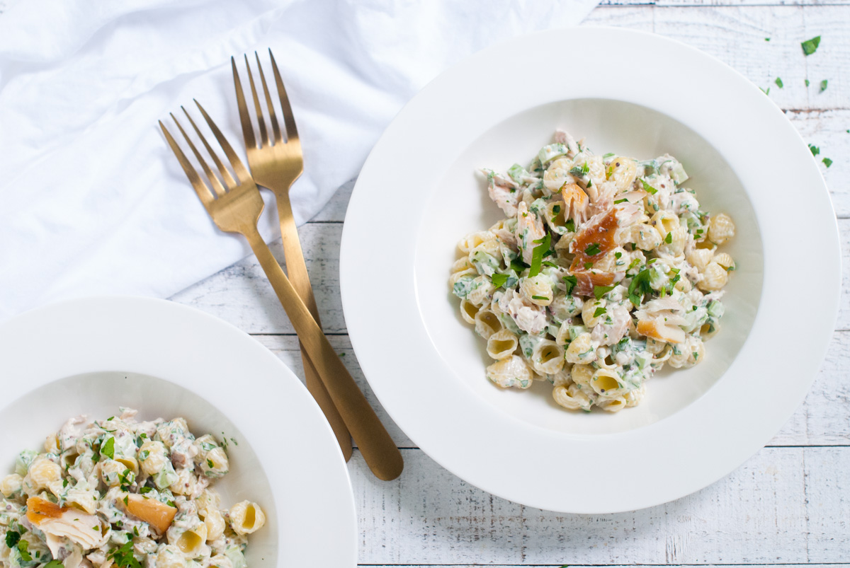 Overhead shot of two bowls filled with shell shapped pasta with smoked trout.